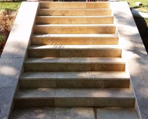 Travertine steps with side walls.